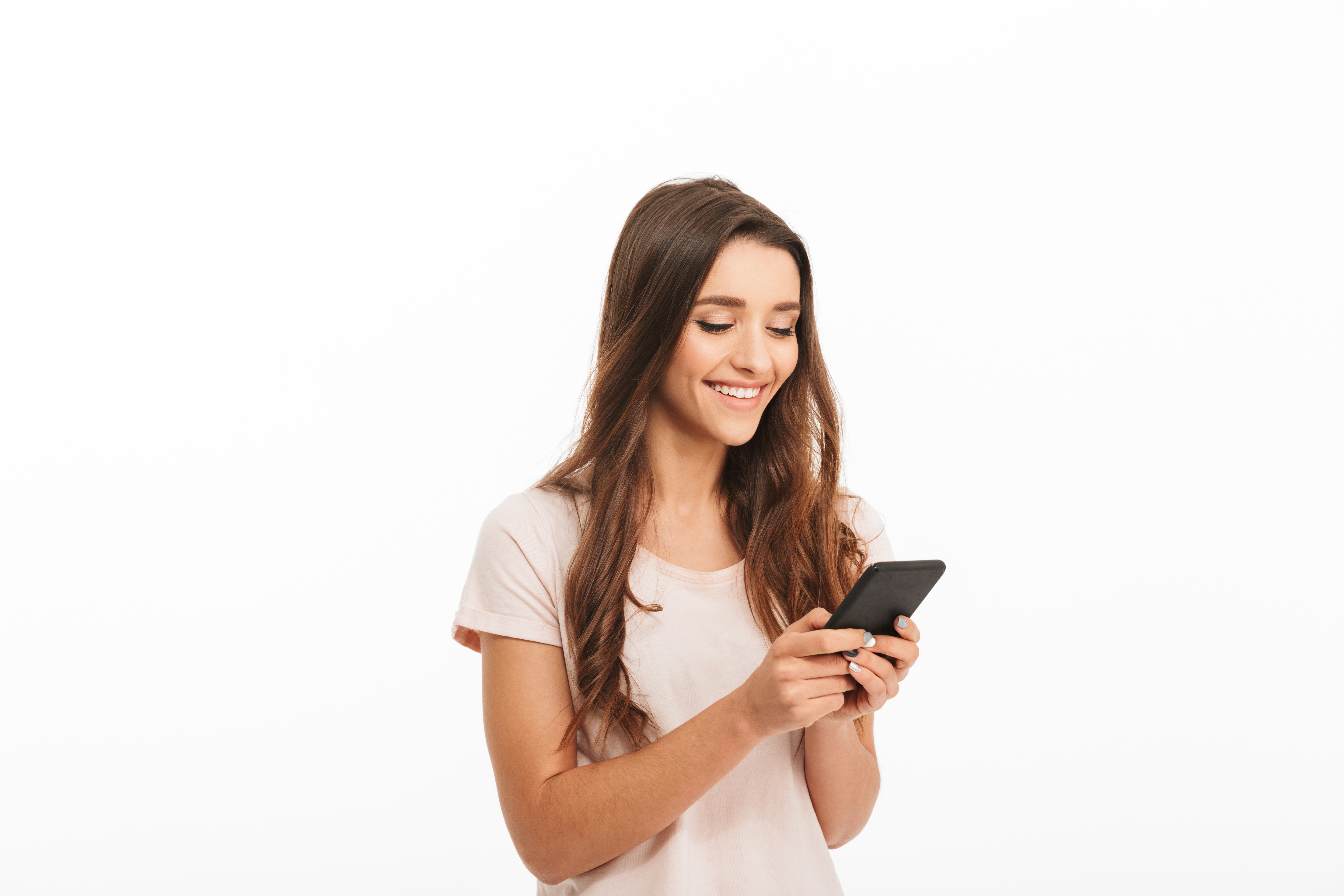 Woman in a white shirt standing, looking at the smartphone in her hands, and smiling.