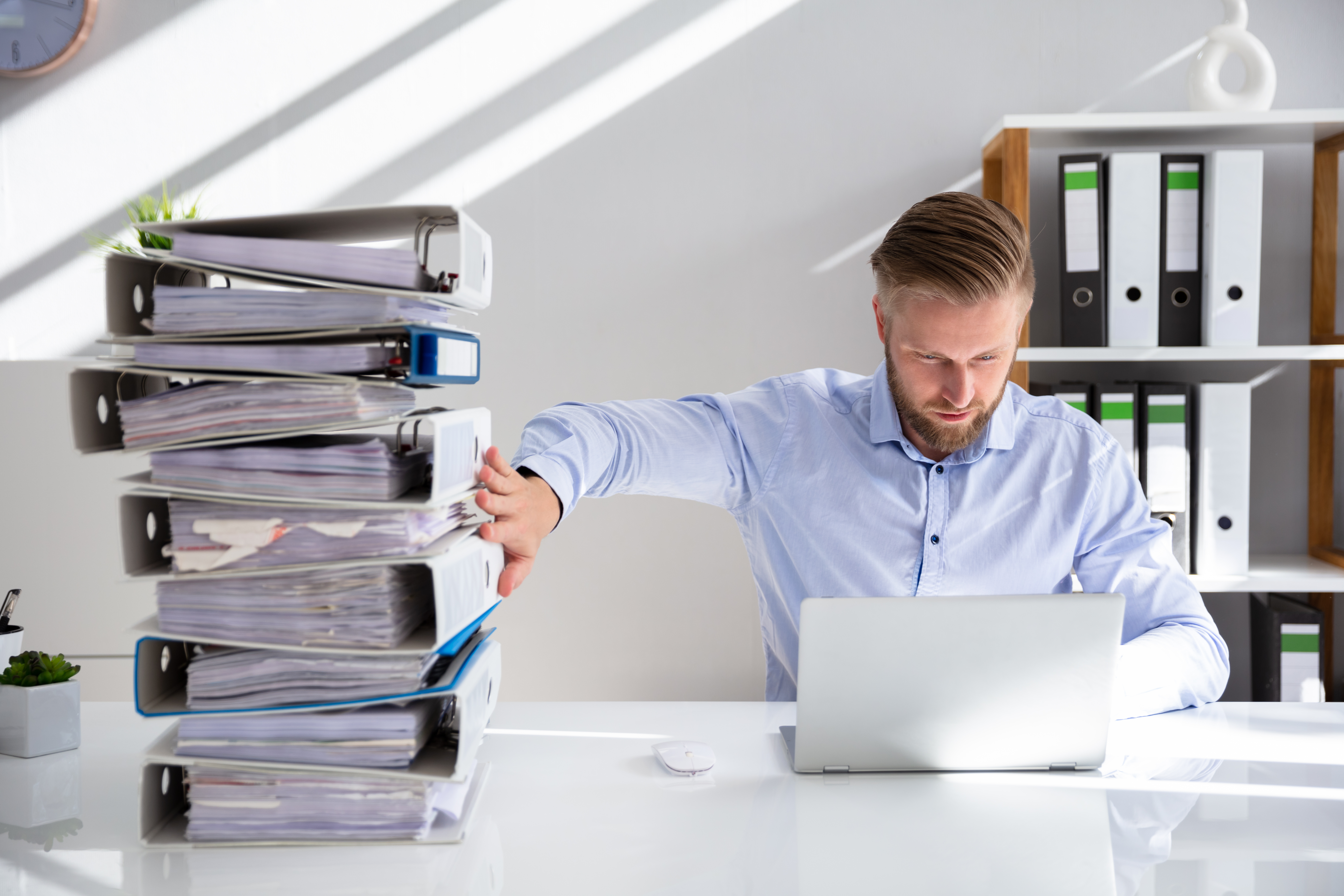 Photograph of a man typing on a laptop and pushing away a large stack of binders full of paper