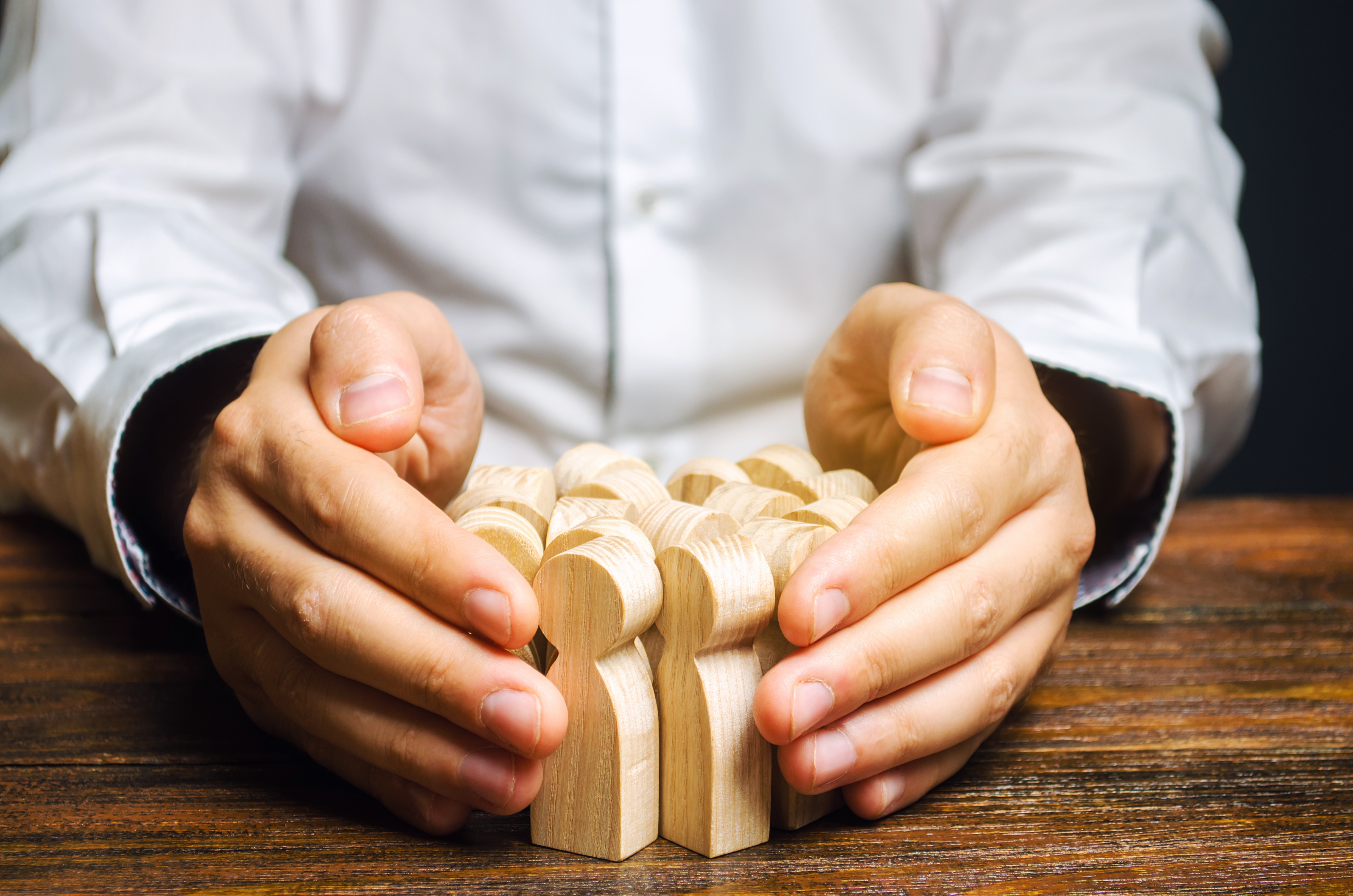 Hands on a table holding a cluster of wooden figurines.