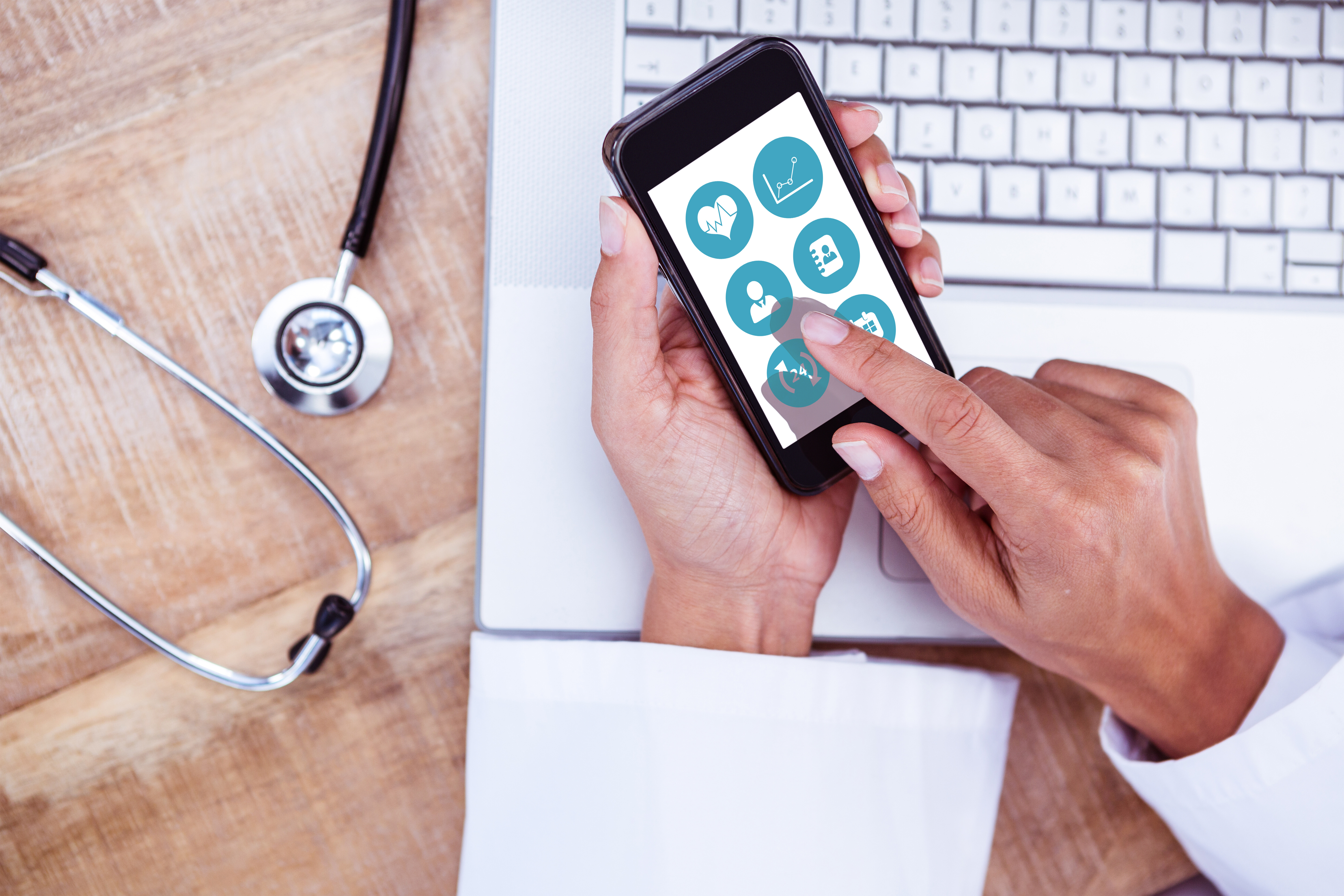 Hands in a white lab coat holding a smartphone that shows some health icons.