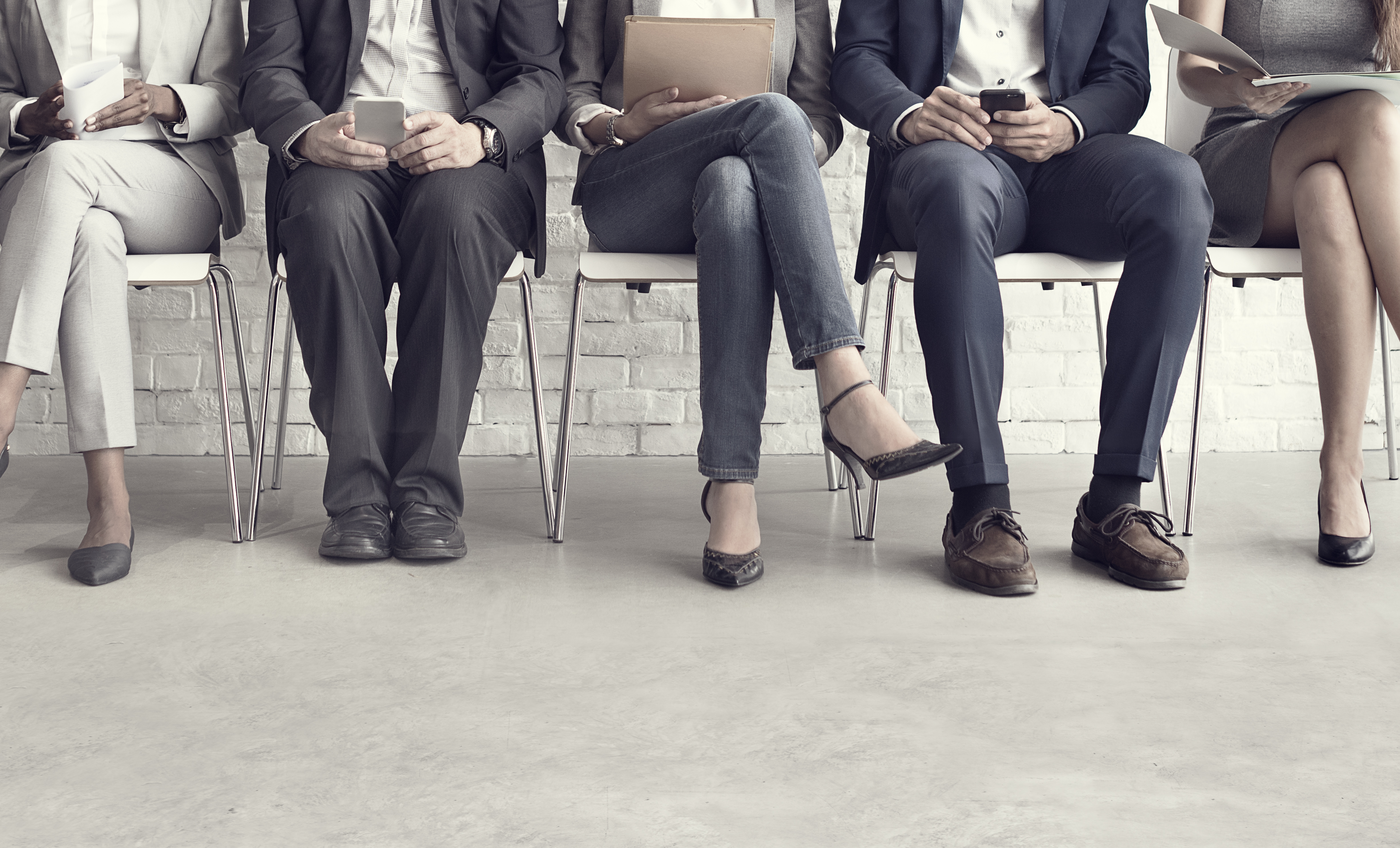 A row of job applicants wearing business clothes sitting in chairs.