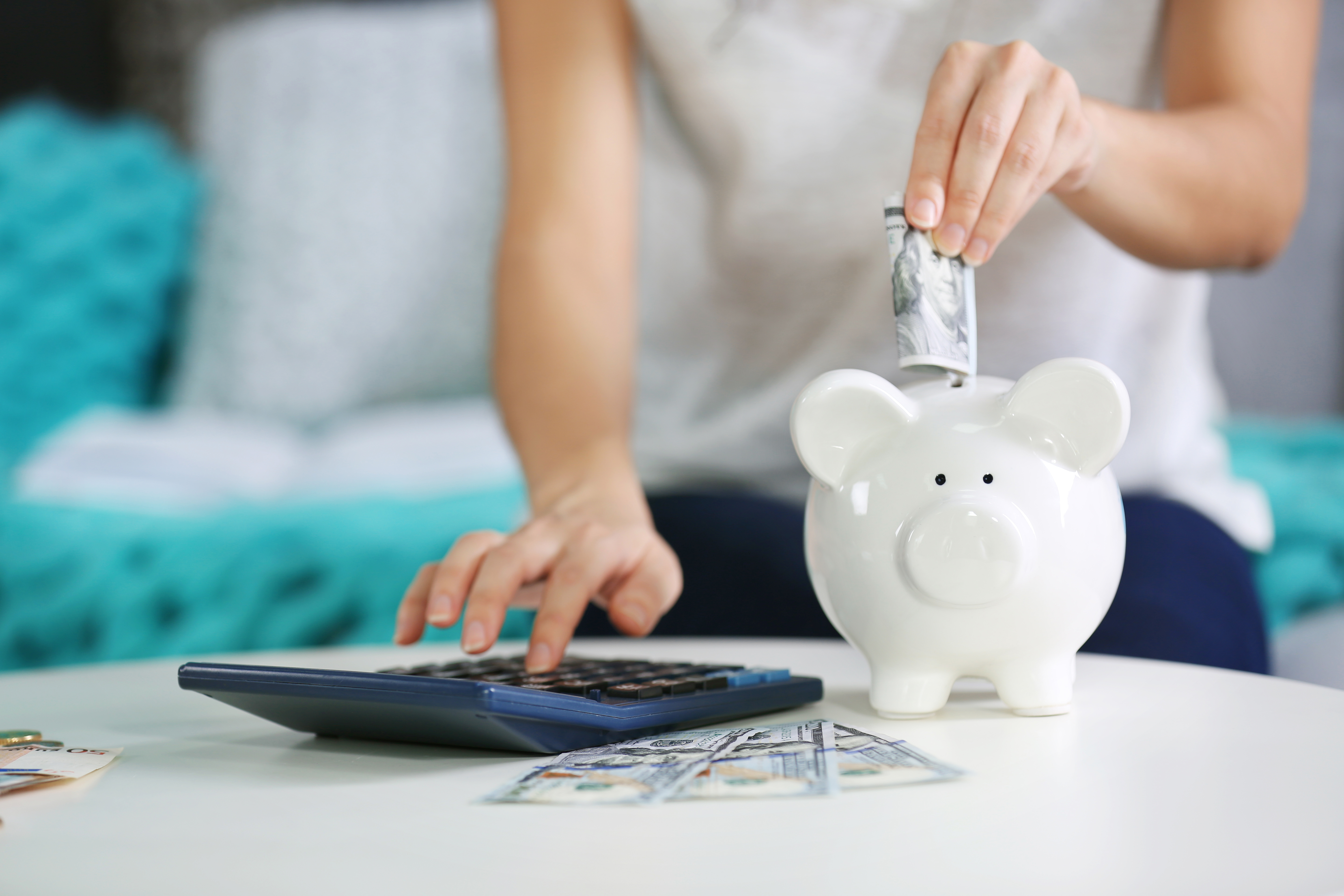 A person sitting down and using a calculator while putting money into a piggy bank with their other hand.
