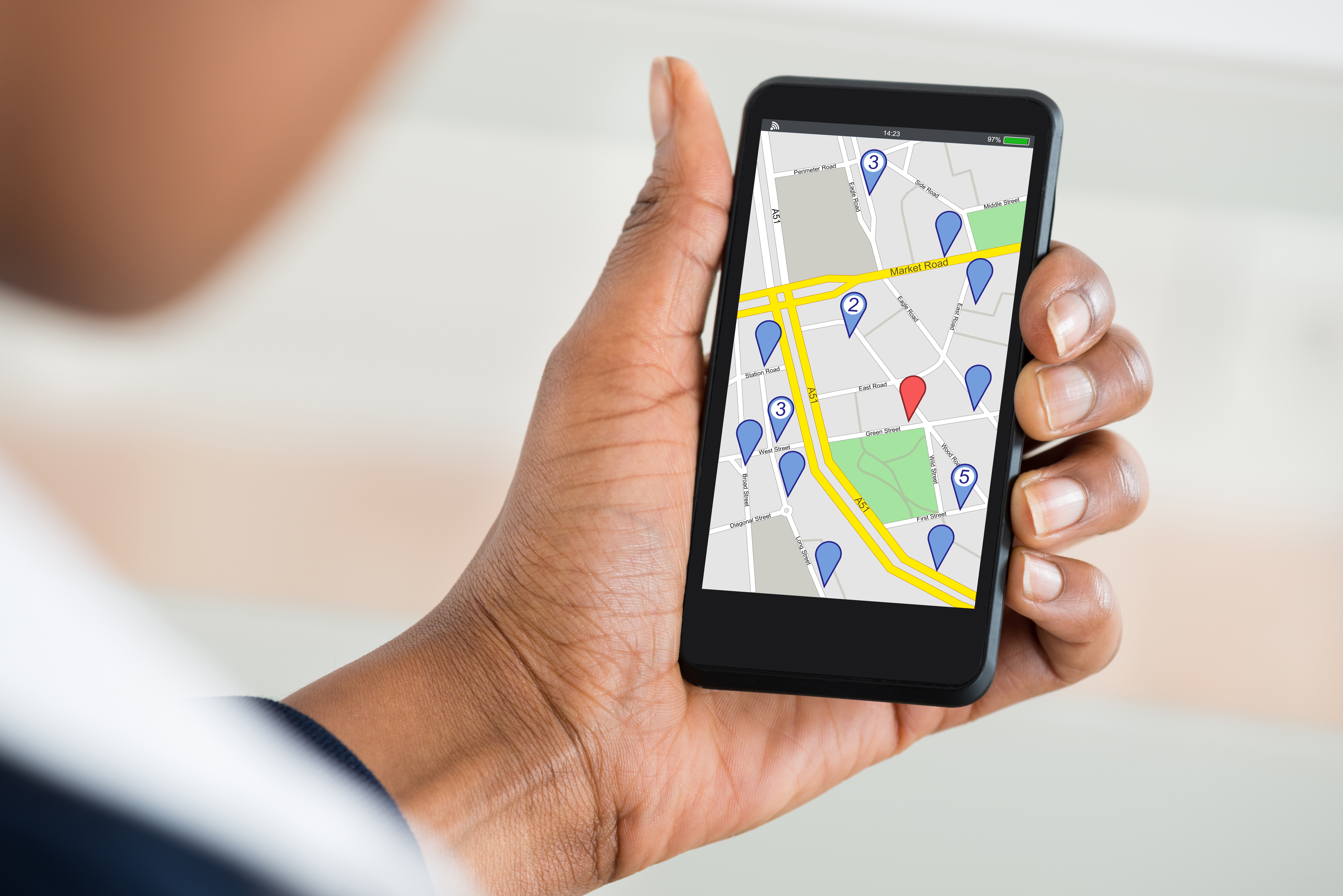A hand holding a phone displaying a map and points of interest.