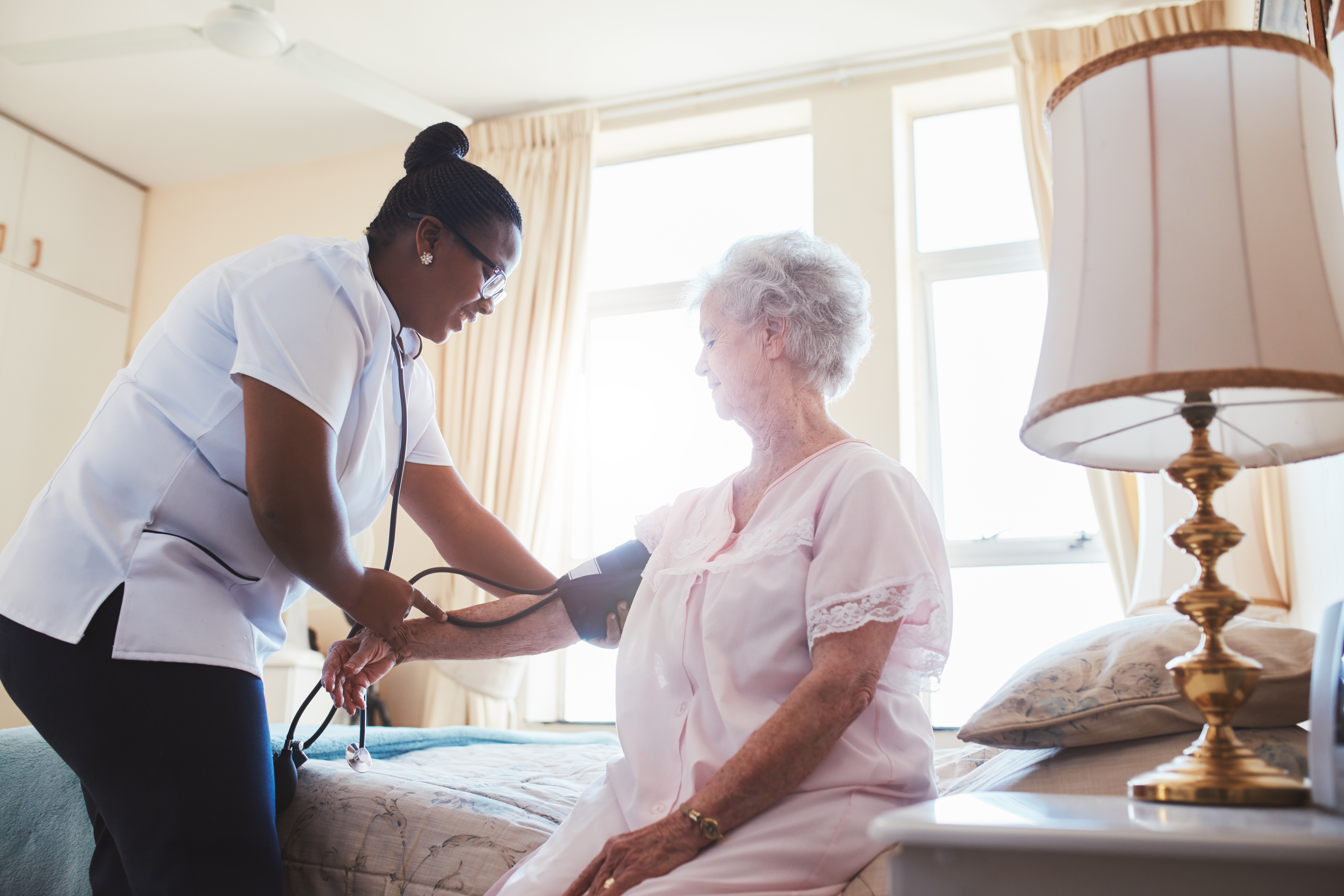 A caregiver taking her patient's blood pressure at home.